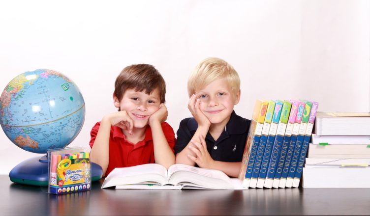 Dwaj chłopcy z przyborami szkolnymi